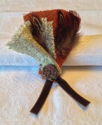 Tweed and felted wool with pheasant feather, velvet ribbon and button trim